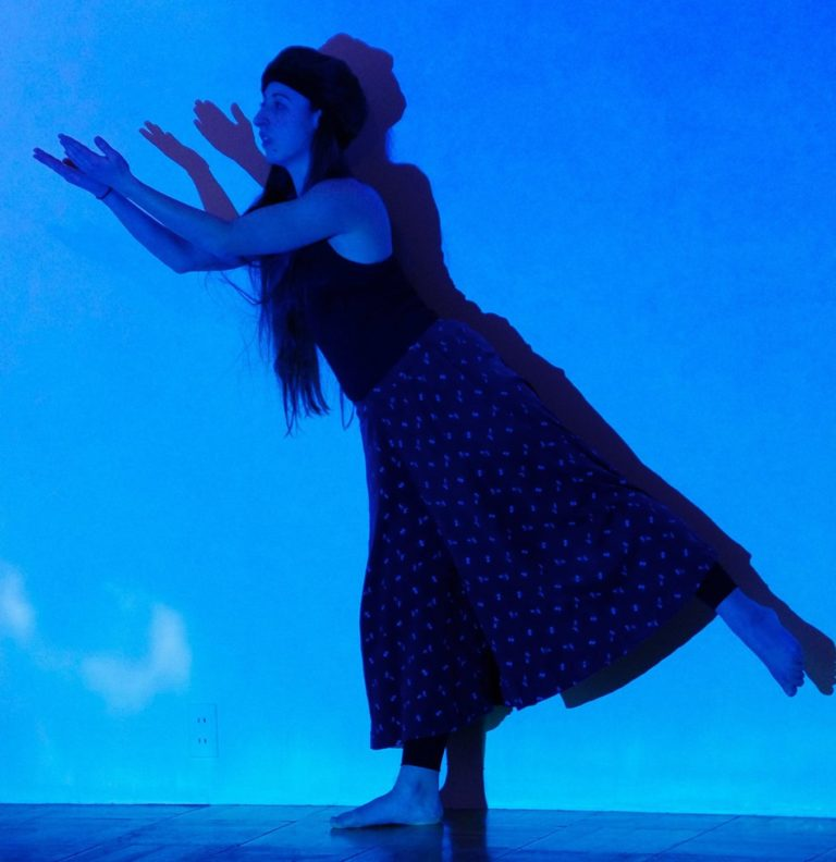 woman dancing in front of a blue sky background